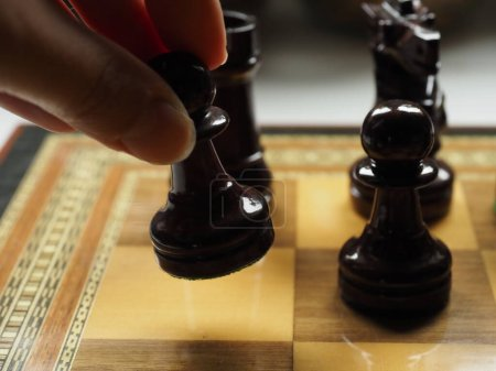 Photo for Fingers taking a piece of a wooden chessboard - Royalty Free Image