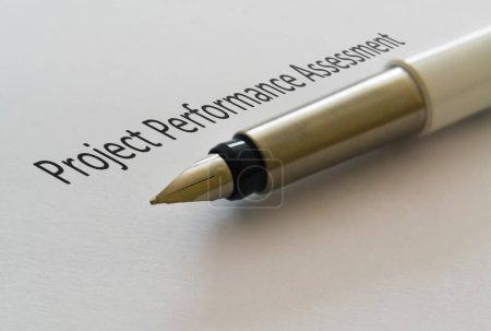 Photo pour Texte Évaluation du rendement du projet et stylo plume sur fond lumineux - image libre de droit