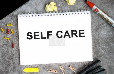 Texto de autocuidado en un cuaderno blanco con alfileres, marcador y grapadora en una mesa de hormigón