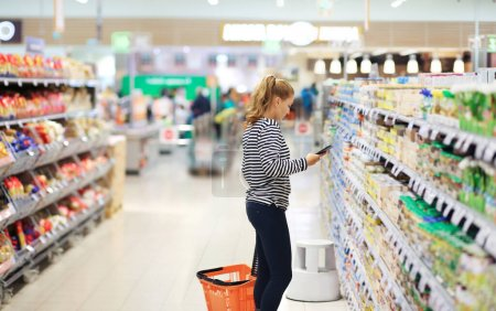 Woman choosing a dairy products at supermarket...