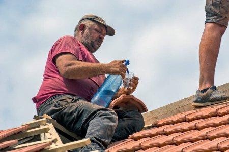 Photo pour Zrenjanin, Serbie, le 23 juillet 2020. Les maîtres travaillent sur le toit d'une maison privée pour remplacer une vieille tuile. Un des maîtres se rafraîchit avec de l'eau gazeuse pendant une pause sur le toit. - image libre de droit