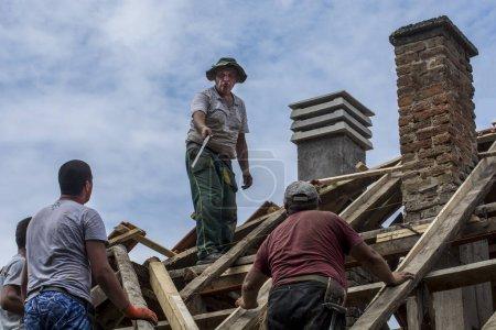 Photo pour Zrenjanin, Serbie, 22 juillet 2020. Un groupe de maîtres travaille sur le toit d'une maison privée pour remplacer une vieille tuile. Ils utilisent une belle journée et un temps stable sans pluie. Ils sont perturbés par divers câbles qui courent sur le toit de la maison. - image libre de droit
