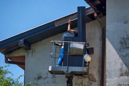 Photo pour Deux maîtres remplacent les draps sur les côtés d'un grand bâtiment. Les travaux sont effectués à partir d'un panier spécial à haute altitude. - image libre de droit