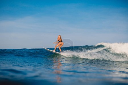 Attractive surfer woman at surfboard ride on wave. Woman in ocean during surfing.