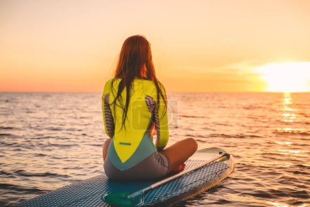 Surf woman posing on the surfboard in ocean at sunset.