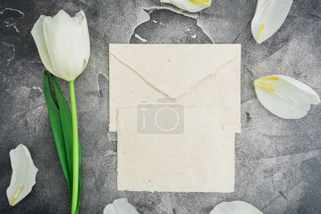 Floral composition with white tulips and paper envelope on stone background. Flat lay, top view.