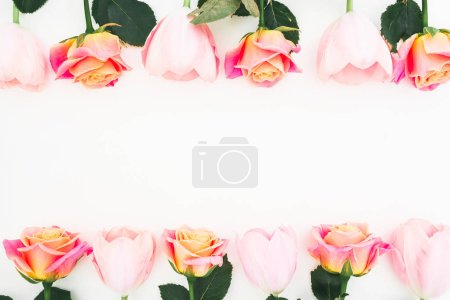 `Floral frame made of roses and tulips flowers and green leaves on white background. Flat lay, top view. Flower background