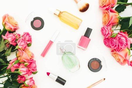 Photo pour Composition beauté avec bouquet de fleurs roses et maquillage cosmétique sur fond blanc. Vue de dessus. Flat lay bureau féminin . - image libre de droit