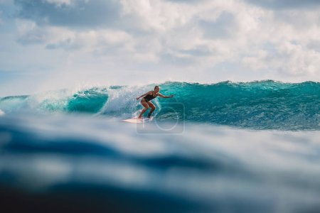 Professional surf girl on surfboard. Woman in ocean during surfing. Surfer and ocean wave