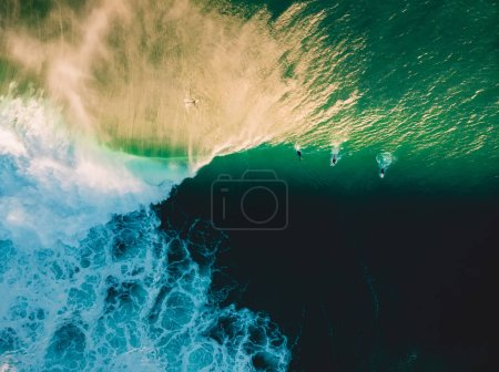 Aerial shooting of surfing at sunset. Surfers and big ocean wave