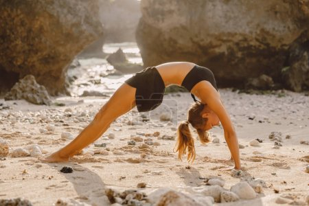 Young woman doing yoga at sandy beach