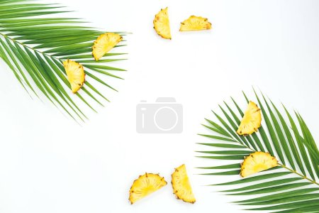Photo pour Cadre avec des tranches d'ananas et des feuilles de palmier sur fond blanc. Couché à plat, vue de dessus. Concept tropical . - image libre de droit