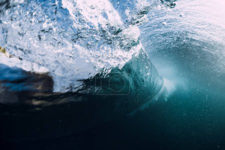 Underwater barrel wave in tropical ocean with sunlight