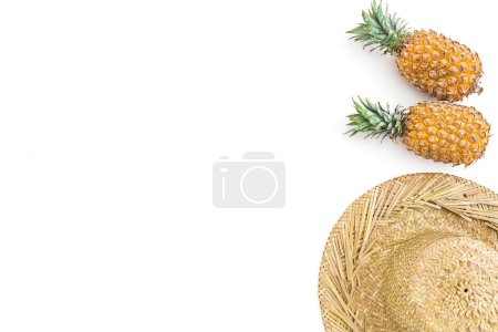 Pineapples and straw hat isolated on white background, top view,Holidays summer concept