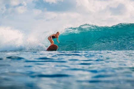 Woman at surfboard ride on wave. Woman in ocean during surfing