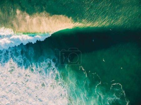 Photo pour Vue aérienne de se briser les vagues dans l'océan avec les internautes et de la lumière du coucher du soleil. Vagues s'écraser sur le récif. Vue de dessus - image libre de droit
