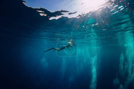 Free diver swimming in ocean, underwater photo with diver and bubbles