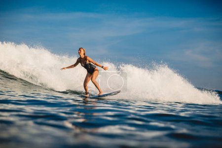 Young surfer woman with surfboard on wave.