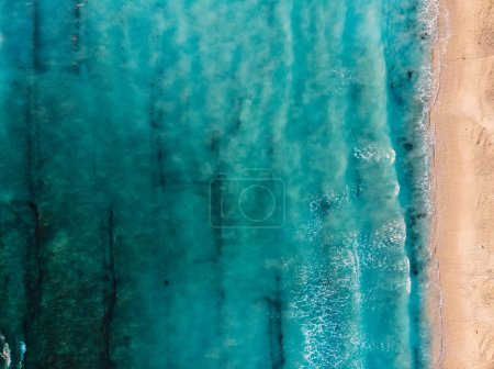 Top view of beautiful beach with turquoise ocean and waves, aerial view