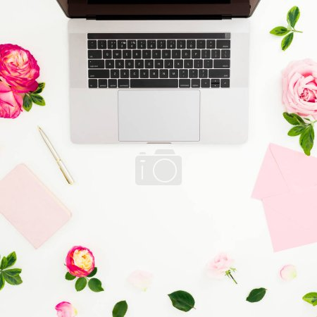 Laptop, roses flowers, diary, pen and envelope on white background. Flat lay. Top view. Feminine composition with copy space