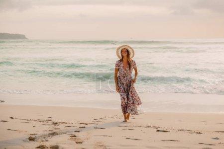 Photo pour Jolie femme en robe d'été sur la plage au coucher du soleil ou au lever du soleil. Style féminin. - image libre de droit