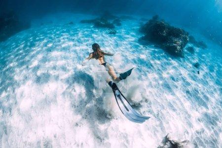 Photo pour Femme plongeur libre avec du sable sur la mer de sable avec des nageoires. Plongée sous-marine à Hawaï - image libre de droit