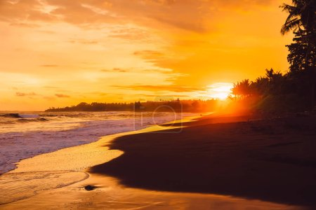 Photo for Warm sunset or sunrise with ocean waves and coconut palms in east coast of Bali - Royalty Free Image