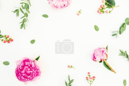 Floral frame with peonies flowers, hypericum and eucalyptus leaves on white background. Flat lay