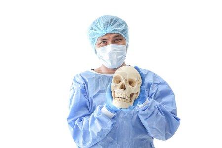 Photo pour Chirurgien en salle d'opération à l'hôpital sur fond blanc. jeune médecin en uniforme posant isolé en fond blanc. Le chirurgien tient le crâne pour expliquer au patient. - image libre de droit