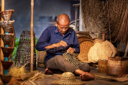 Photo pour Artisans de Thaï. Un vieil homme qui est l'artisanat dans la province de Buriram Tisser un panier de bambou. Artisanat qui a été exercé depuis les temps anciens. - image libre de droit