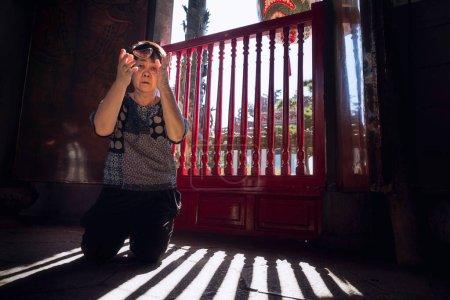 Photo pour Une femme asiatique âgée fait fortune dans un célèbre sanctuaire de Taiwan. Le bois rouge pour faire fortune est une croyance chinoise. - image libre de droit