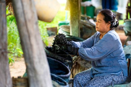 Photo for Craftsmen of Thai indigo cotton. Indigo in the jar Indigo is used for dyeing cotton in natural colors. Is the wisdom of Thailand - Royalty Free Image