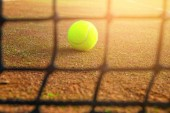 close-up tennis ball and net on court with sunlight in background