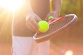 A tennis player prepares to serve a tennis ball during a match with sunlight in background
