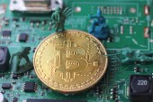 Bitcoin under attack four miniature men surrounded by pile of bitcoin. Miniature figurine toys standing near bitcoin