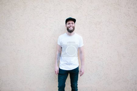 Hipster handsome male model with beard wearing white blank t-shirt and a baseball cap with space for your logo or design in casual urban style