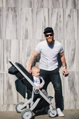 Photo for Father walking with a stroller and a baby in the city streets - Royalty Free Image