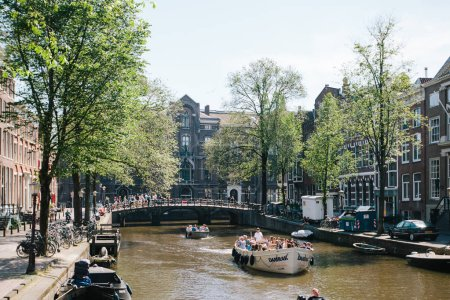 NETHERLANDS, AMSTERDAM - JUNE: 15,2017: Veiw on the bridge through the river channel with a touring boat, picture of canals in Amsterdam