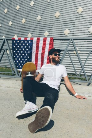 Happy hipster man holding American or USA  flag. He is wearing casual clothes