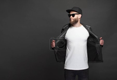 Photo for Hipster handsome male model with beard wearing white blank t-shirt and a baseball cap with space for your logo or design in casual urban style - Royalty Free Image