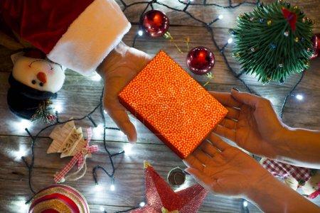 Photo pour Santas main offrant une boîte-cadeau à une femme dans un dcor de Noël traditionnel - image libre de droit