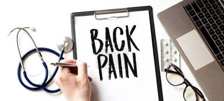 Arzt schreibt einen Text ZURÜCK PAIN auf den Pappteller, medizinisches Konzept