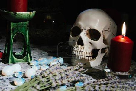 Zbliżenie drewniany stół z okultystyczny atrybut. Kamienie runiczne, świece, sucha lawenda, czaszka, różańce