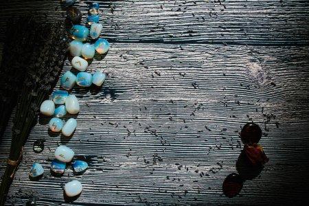 Drewniany stół o okultystycznych atrybutach, widok z góry. Kamienie runiczne, sucha lawenda. Puste miejsce na kopię