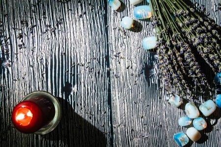 Drewniany stół o okultystycznych atrybutach, widok z góry. Kamienie runiczne, świece, sucha lawenda, różańce. Puste miejsce na kopię