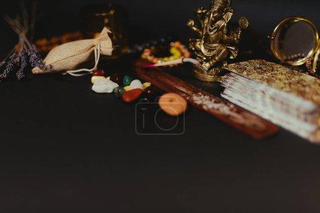 Tabela z okultystycznymi atrybutami, widok z góry. Figurka Ganesha, kamienne różańce, świece, kij aromatyczny