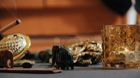 Stolik z okultystycznymi atrybutami, kamienne różańce, świece, kij aromatyczny