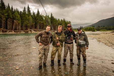 A happy group sport fly fisherman friends on a bea...