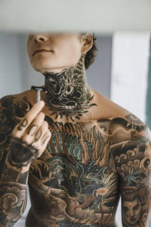 Photo for A young handsome tattooed man in the morning shaves in front of a mirror, a razor in his hands, a shave. - Royalty Free Image