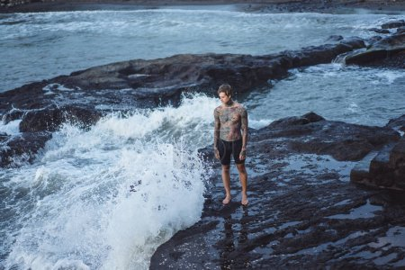 Photo for A tattooed man on the edge of a cliff. splashes of ocean waves. - Royalty Free Image